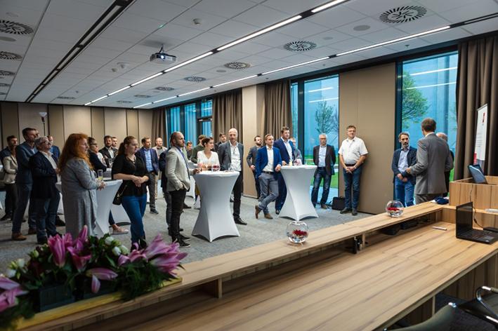ľudia stojaci v konferenčnej miestnosti pri vysokých stolíkoch na otvorení novej kancelárie