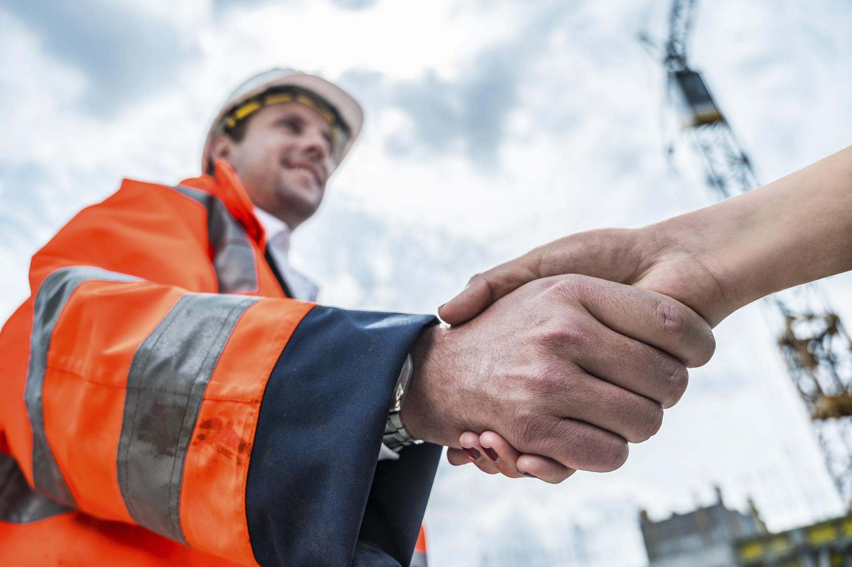 Podané ruky vyjadrujúce spolupráci so spoločnosťou DELTA Group